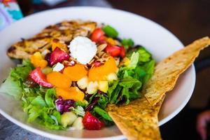 Healthy salad with grilled chicken and fruits