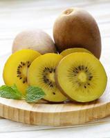 ripe yellow kiwi on a wooden board