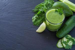 Green smoothie and ingredients - avocado, apple, cucumber, kiwi, lemon photo