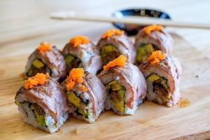 grelha de carne rolo sushi na placa de madeira