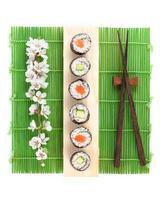 Sushi maki set with salmon and cucumber and sakura branch photo