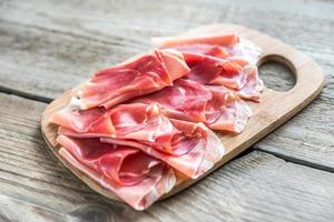 Slices of jamon on the wooden board photo