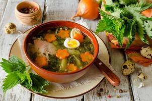 sopa de ortiga con huevos y zanahoria en el tazón foto