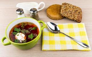 Borsch, bread, spices, spoon on napkin and sour cream