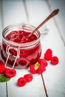 Raspberry jam in a jar on wooden background photo