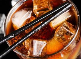 glass of cola with ice cube photo