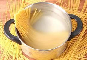 Cook the spagetti in pan on wooden background close-up