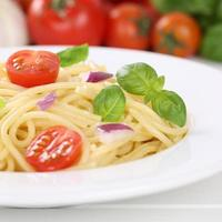 Italian cuisine spaghetti noodles pasta meal with tomatoes on plate