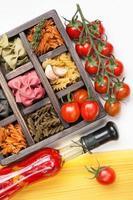 Mix Italian pasta and spaghetti tomatoes in wooden box photo