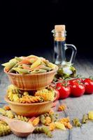 Raw eliche and penne tricolori pasta in the wooden bowls photo