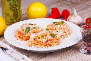 Pasta with tomato sauce, parmesan cheese and mint photo