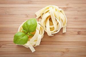 Nido fettuccine de pasta italiana en tabla de cortar foto