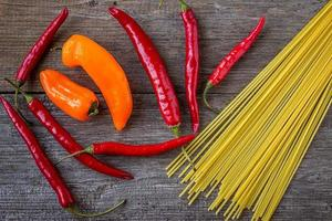 Red hot pepper and spaghetti on old wooden table photo
