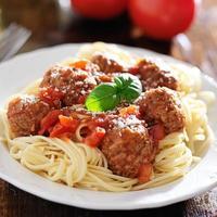 spaghetti and meatballs with basil garnish photo