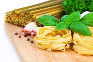 Italian pasta fettuccine nest with garlic and fresh basil leaves photo
