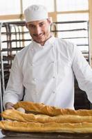 panadero mirando baguettes recién horneadas foto