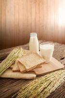 Vaso de leche y pan integral sobre tabla de madera foto