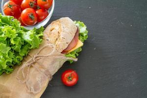 Summer sandwich with ham, cheese, salad and tomatoes photo