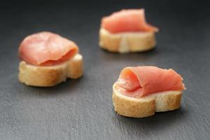 rebanadas de baguette con salmón curvo sobre fondo de pizarra