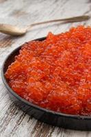 Red caviar in a black plate over a vintage background photo