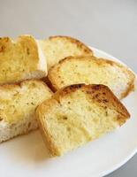 Garlic bread slices on white plate