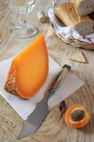 Mimolette cheese, baguette and wineglass photo
