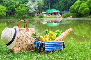 Picnic basket with fruits, bread and hat on straw bag