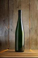 Simple wine bottle in front of wooden wall