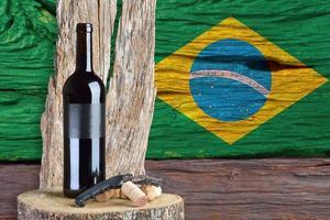 Botella de vino con la bandera de Brasil en el fondo foto