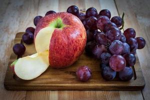 manzana y uvas en una tabla de madera