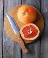 pomelos maduros y cuchillo en tabla de cortar, sobre fondo de madera