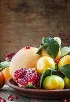 Plato de arcilla con frutas de invierno: pomelo, mandarinas, caquis foto