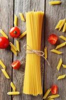 espagueti con tomate sobre fondo de madera gris foto