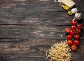 Pasta, tomatoes and garlic on wooden table background with copy