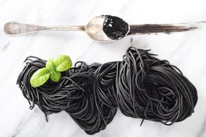 Squid ink homemade pasta on marble photo