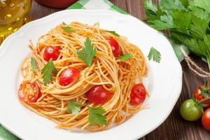 Spaghetti pasta with tomatoes and parsley photo