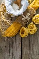 Pasta and wheat on rustic wood background