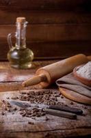 mesa de estilo rústico con pasta, harina y aceite. foto