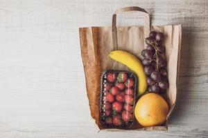 fresa con diferentes frutas dentro de una bolsa de papel horizontal foto