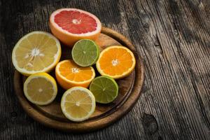 Halves of citrus fruits on wooden background