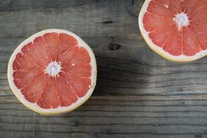 Sliced Grapefruit halves on a wooden table