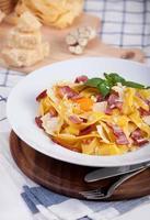 Pasta carbonara with tagliatelle spaghetti, egg yolk, bacon and basil.