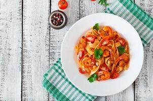Fettuccine pasta with shrimp, tomatoes and herbs photo