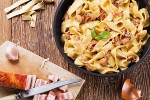 pasta carbonara con tocino, albahaca y queso