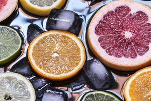 Sliced citrus fruits lemon, lime, orange, grapefruit with ice ov
