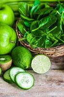 Mix of green fruits and vegetables on rustic wooden background photo