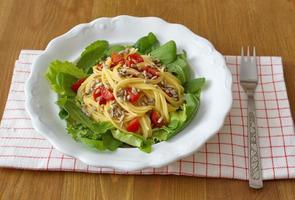 El almuerzo saludable consiste en espagueti de maíz, ensalada, semillas y tomates.
