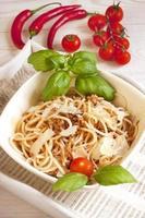espaguetis a la boloñesa en plato blanco, mesa de madera