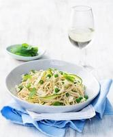 Pasta with olive oil, green vegetables and glass of wine