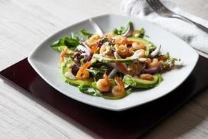 Salad with avocado and shrimps on square ceramic plate  horizontal